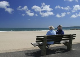 two people sitting on a bench looking at the sea