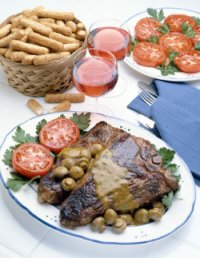 steak on a plate with chips and tomato