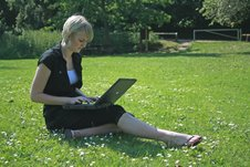 lady sitting on grass using laptop