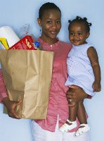 lady carrying a small child and grocery bag
