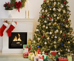 decorated christmas tree, fireplace and stocking hanging from mantleshelf