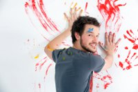 man painting hand prints on wall