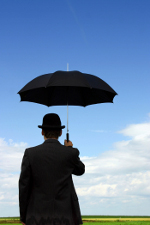 man holding umbrellal under clear blue sky