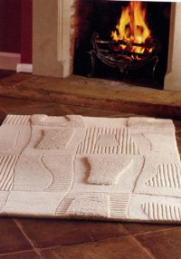 white sculptured rug in front of hearth